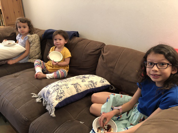 Sisters sit on the couch with snacks