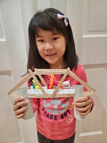 the girl has toys crossing the bridge she made