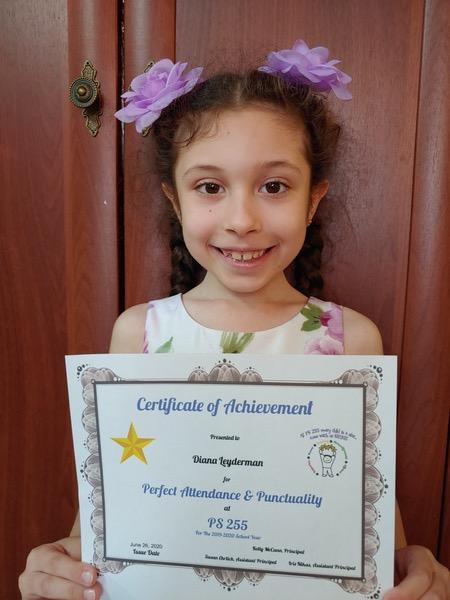 child holding certificate smiling in front of door