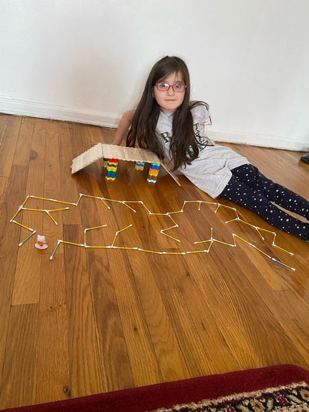 the child lays next to her bridge on the floor and the constellation she created