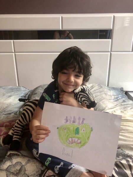 child sitting on a bed holding drawing