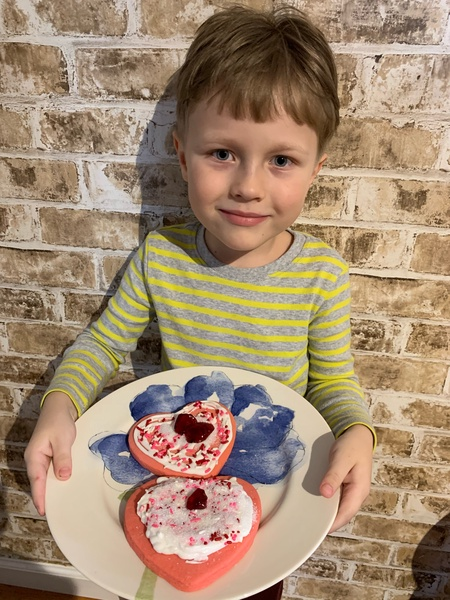 student in green shirt shows their decorated heart shaped cookies with sprinkles
