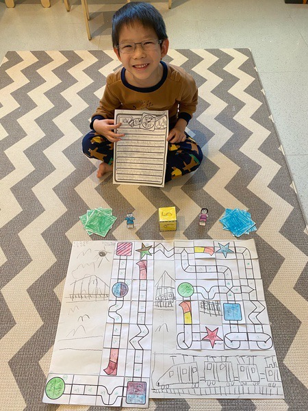 child sits on the carpet behind the board game they created