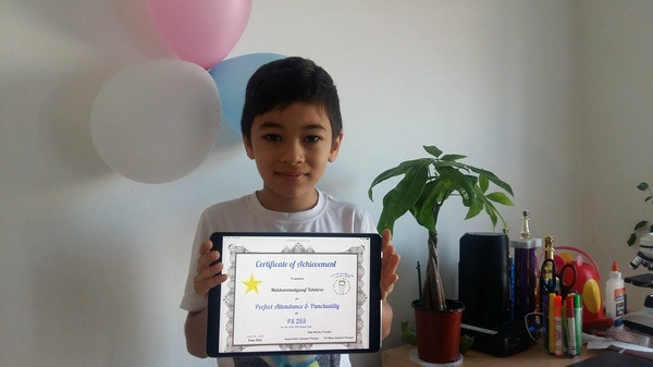 boy holds certificate in front of balloons