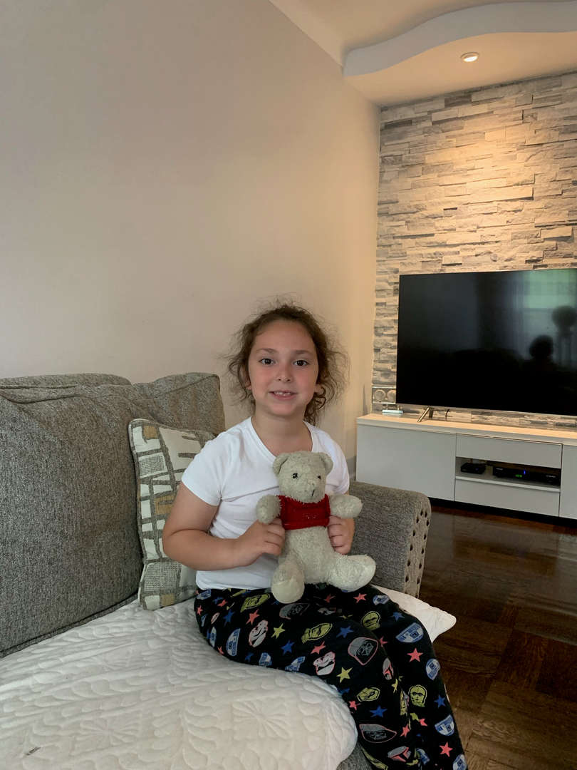child sitting on a couch in the living room holding stuffed animal