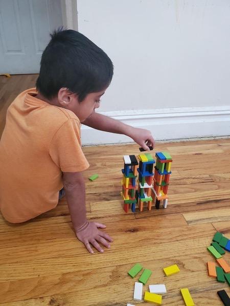 boy in orange shirt builds