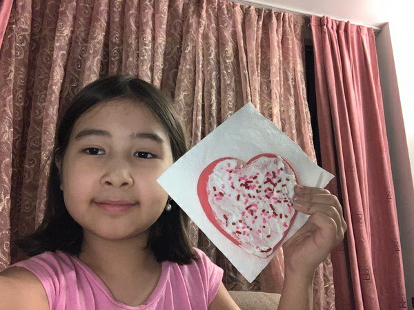 girl holds up heart decorated cookie