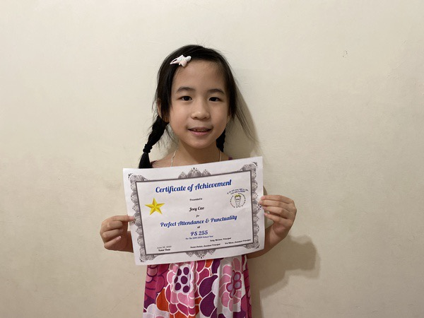 child standing in front of white wall with certificate