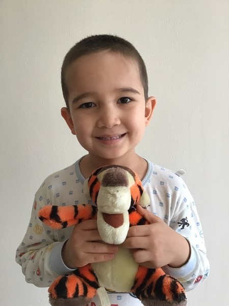 child smiling at camera holding a stuffed Tigger