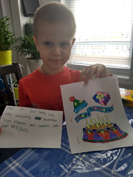 boy holding his drawing and writing