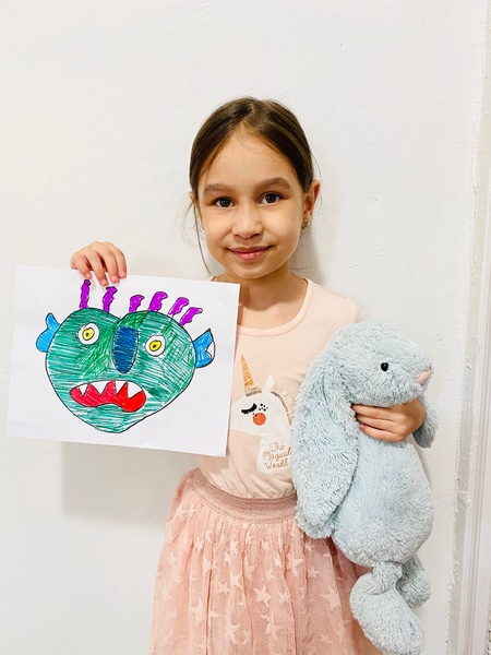 the child holds a blue bunny and her monster drawing