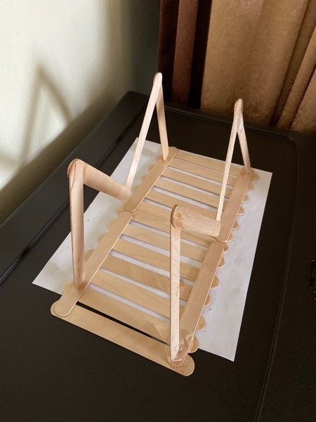 the wooden bridge is on top of a piece of paper