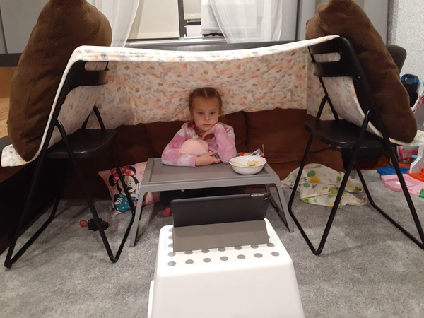 Child watching a movie in a tent fort