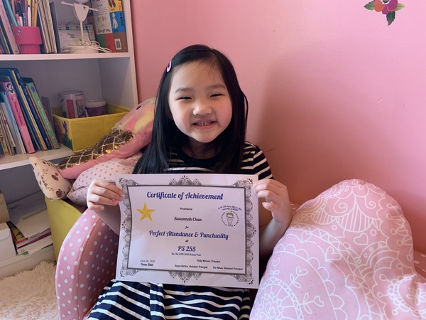 girl sitting in a pink room holds up her certificate