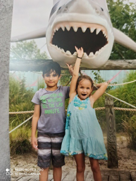 children pose under a shark