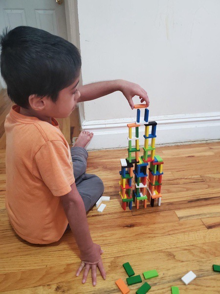 boy continues to built wearing an orange shirt