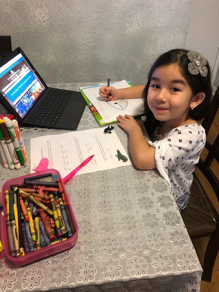 girl does her work as she smiles