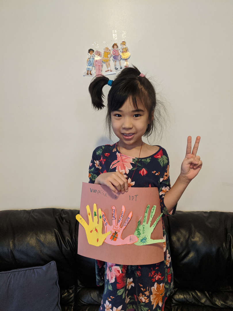 girl holding a family project with three hands