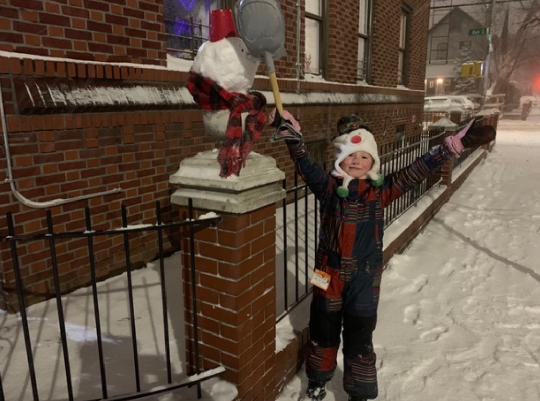 child with their snowman built on the fence