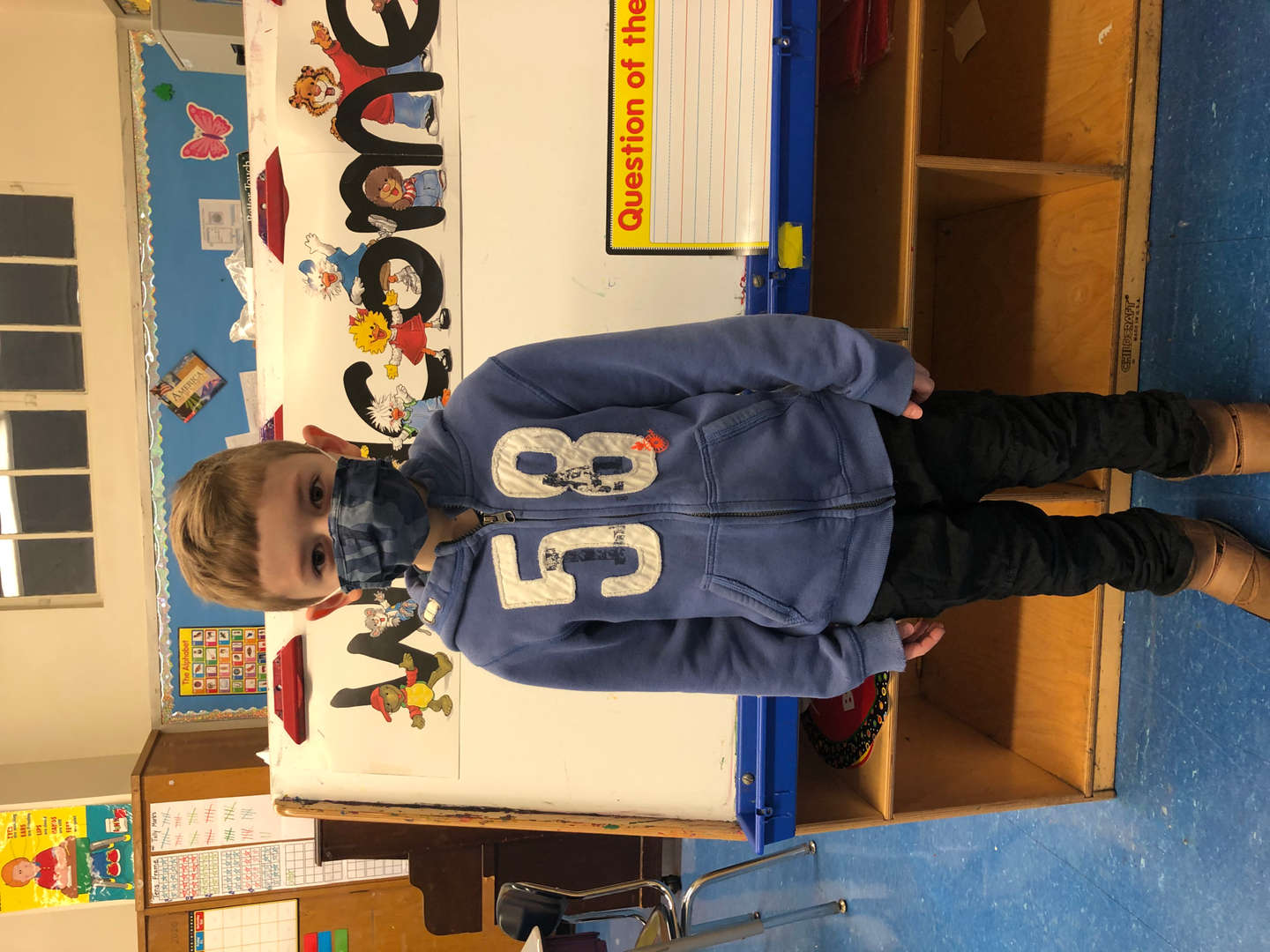 student wears blue sweatshirt with the number 53