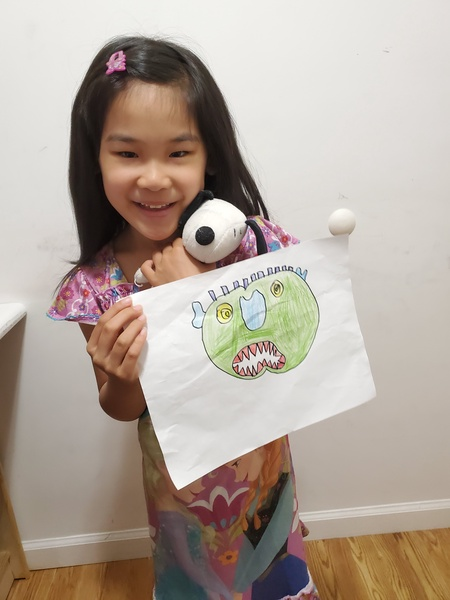 child standing holding drawing of her monster and Snoopy