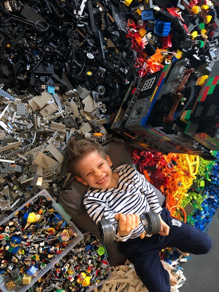 boy lays smiling in a lot of legos