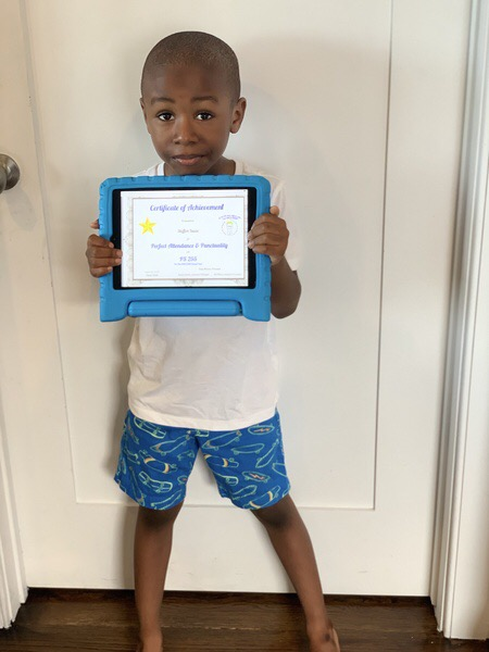 child wearing shorts and a t shirt holds up his certificate