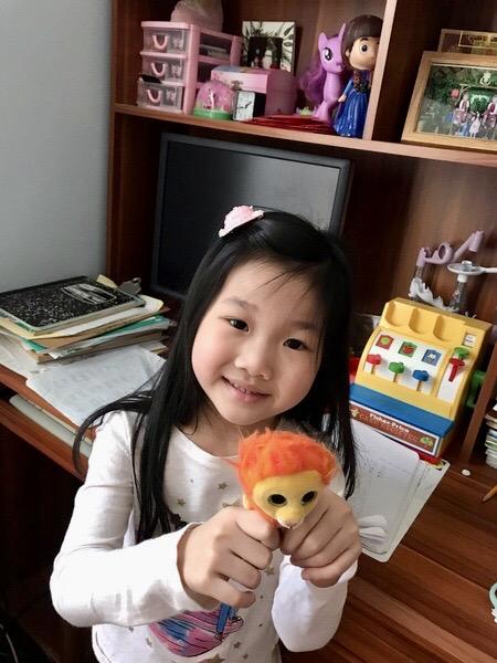 girl holding orange haired stuffed animal