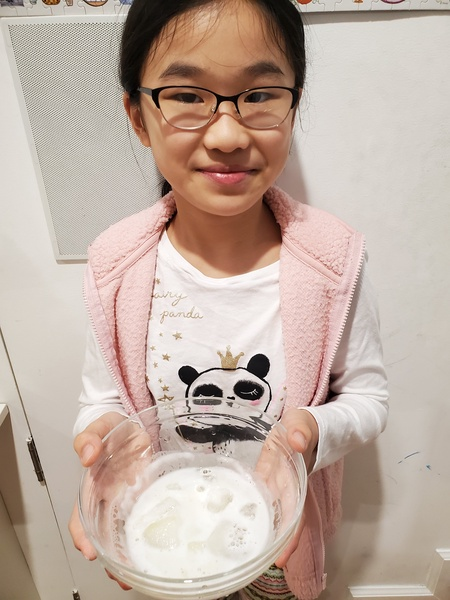 girl holds a bowl with white liquid