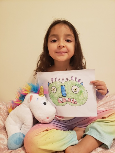 chid holds her monster drawing and stuffed unicorn