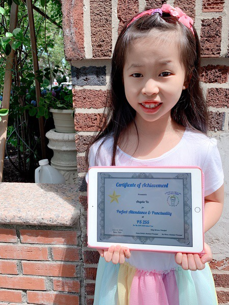 child holds certificate displayed on an iPad outside
