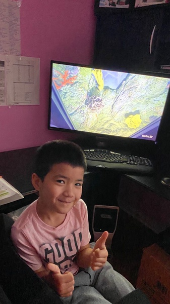 boy smiling as he sits in front of the computer