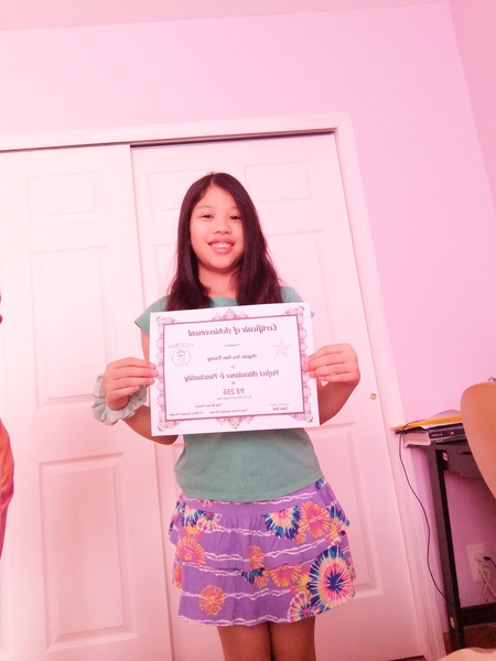 child holds up her award for perfect attendance and punctuality