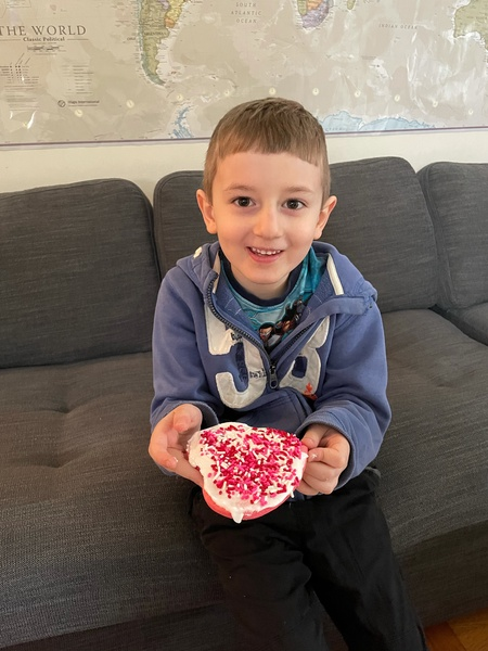 boy in blue sweatshirt showing his decorated cookie