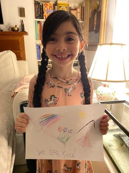child braids holds her work