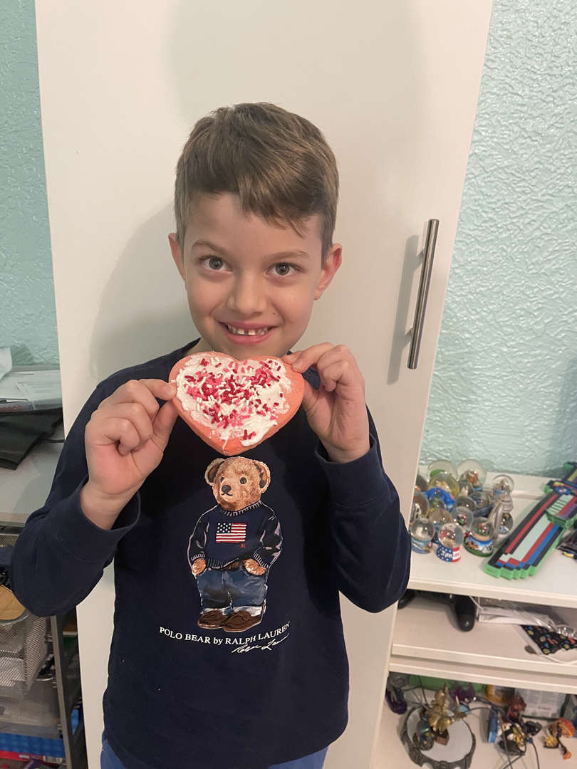student in teddy bear shirt showing his decorated cookie