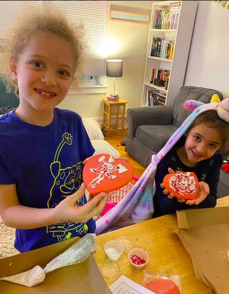 siblings showing their finished cookies