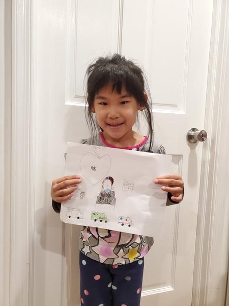 girl holds her work in front of the door