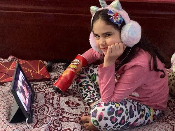 Girl with unicorn headphones and chips watching iPad