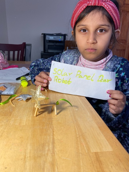 the child holds a label for her project