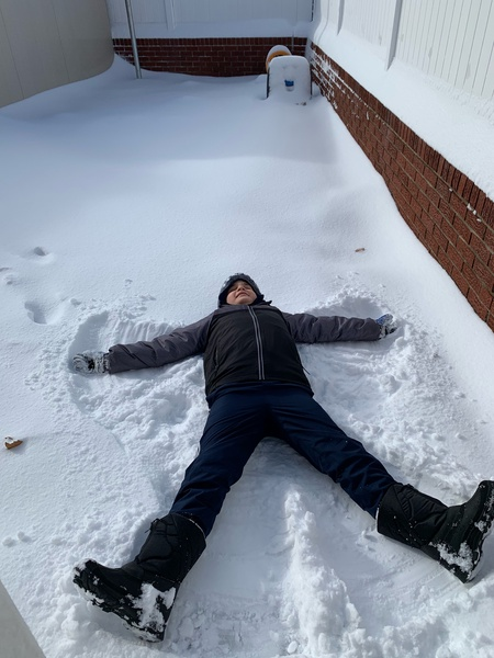 boy making a snow angel in the snow