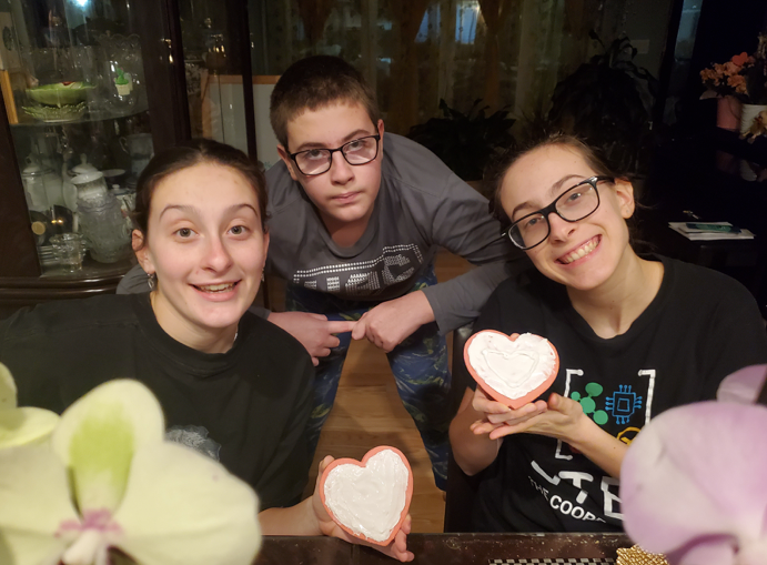 2 sisters and a brother with heart cookies