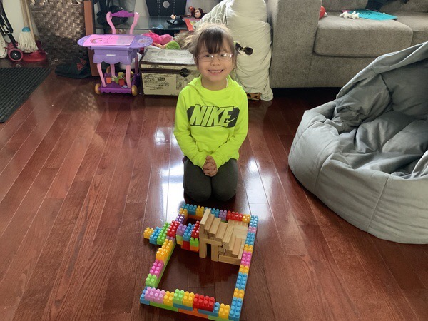Student shows house built from blocks and Legos