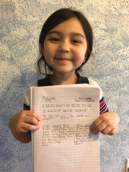 child smiles with her work