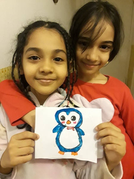 the children hold a picture of a penguin