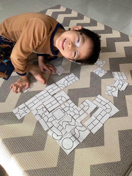 child smiles as he works on putting together the board game pieces