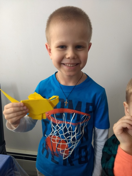boy smiles with his origami