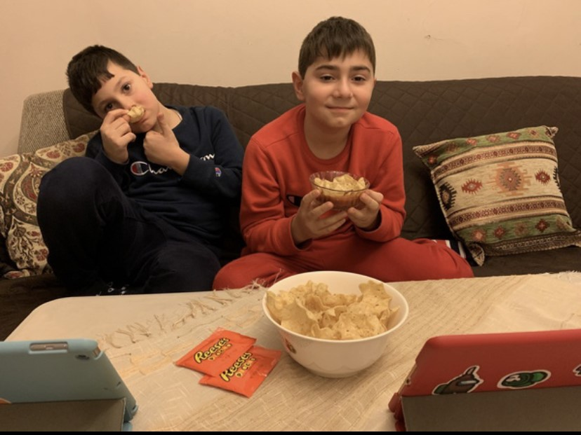 Two siblings watching tv with snacks