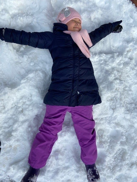 girl happily laying in the snow