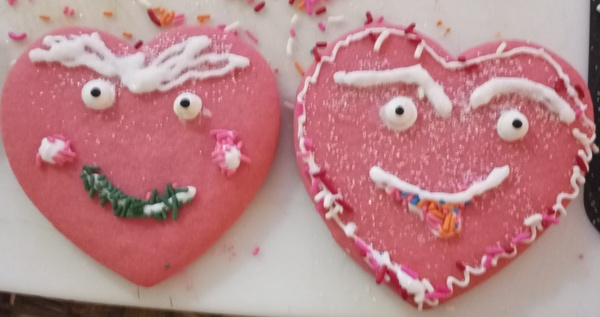 Two decorated heart cookies with faces